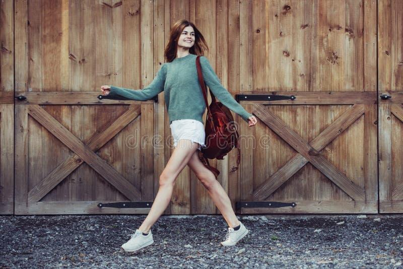 Счастливая девушка битника идя около шортов деревянной стены амбара нося, свитера и коричневого кожаного рюкзака стоковое фото rf