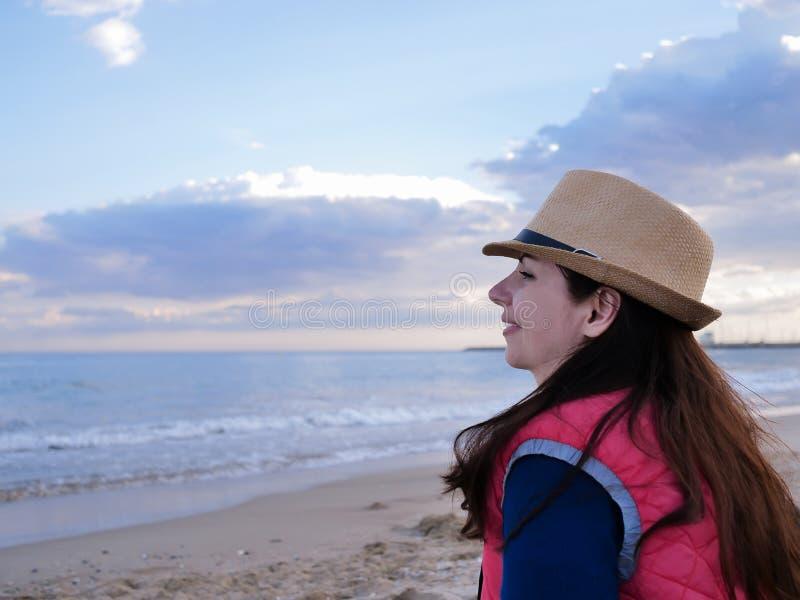 Счастливая девушка брюнета сидя на пляже около моря стоковые изображения