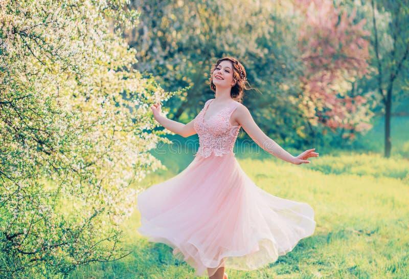 Счастливая девушка вкратце летая нежный розовый смех платья joyfully, водовороты принцессы куклы в ярком желтом саде весны с стоковое фото