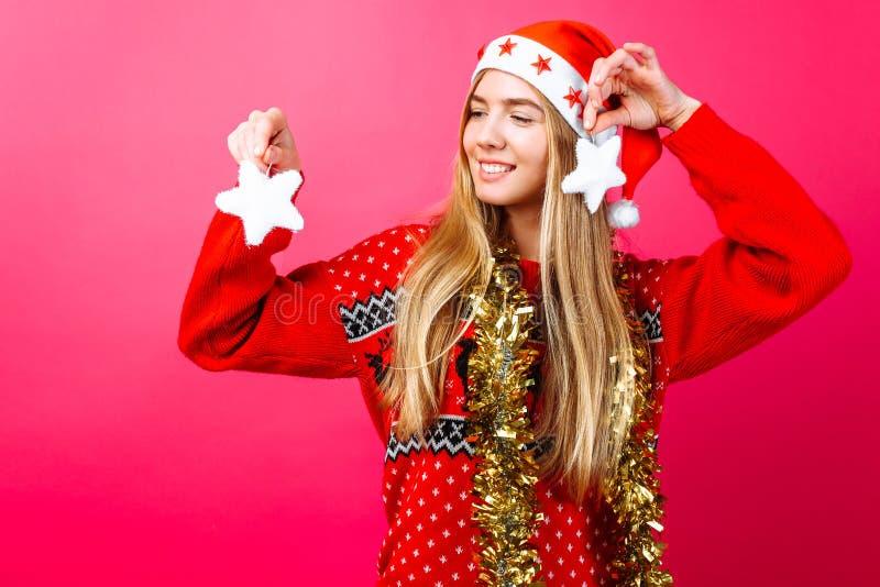 Счастливая девушка в красном свитере и шляпа Санты держа рождество играют главные роли d стоковое изображение