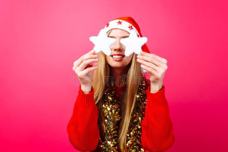 Счастливая девушка в красном свитере и шляпа Санты держа рождество играют главные роли d стоковая фотография