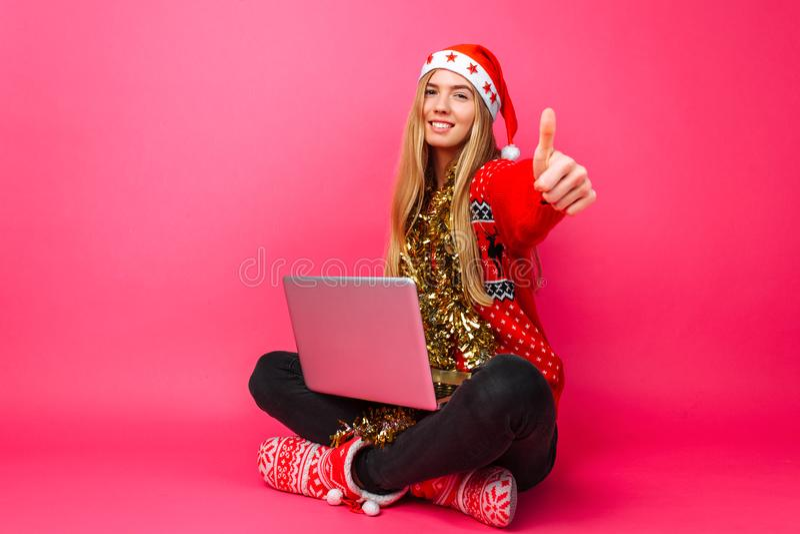 Счастливая девушка в красном свитере и шляпе Санты, сидя с компьтер-книжкой и стоковые изображения rf