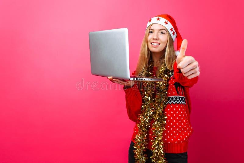 Счастливая девушка в красных свитере и шляпе Санты, стоя с lapto стоковое фото
