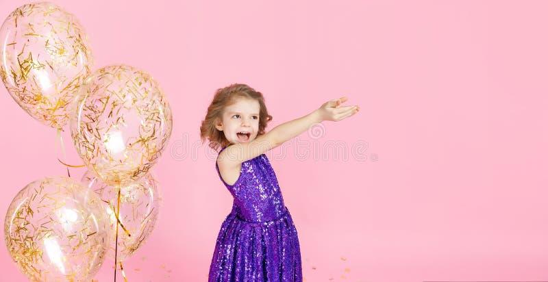 Счастливая девушка в розовом платье празднуя стоковая фотография