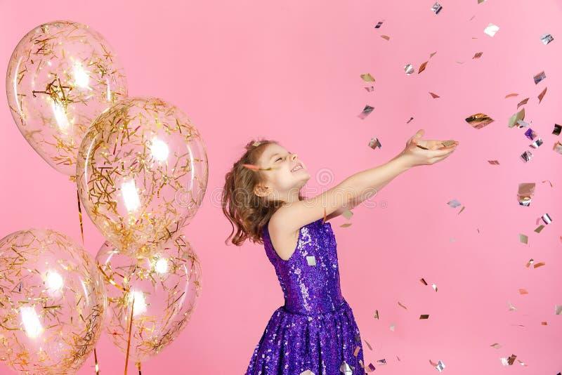 Счастливая девушка в розовом платье празднуя стоковое изображение