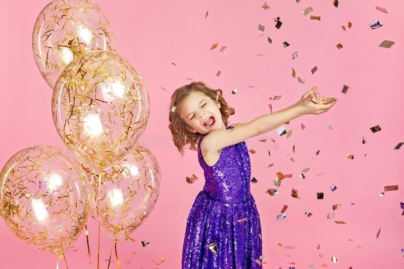 Счастливая девушка в розовом платье празднуя стоковые фото