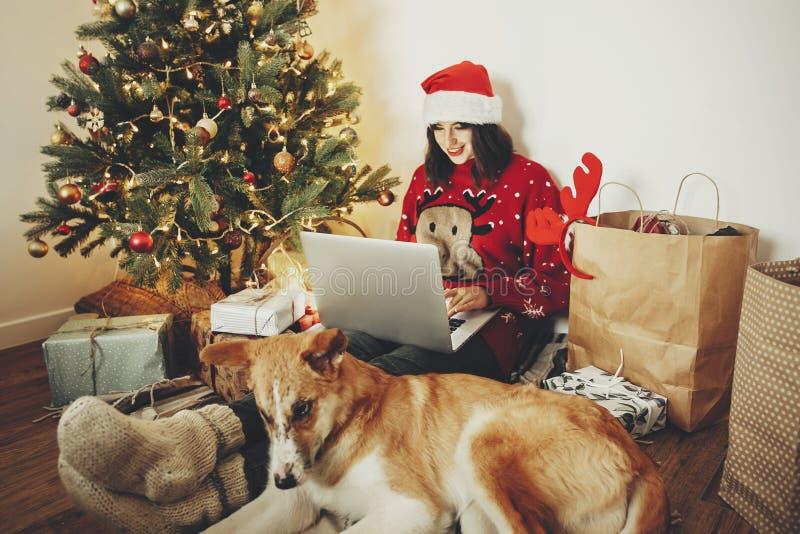 Счастливая девушка в шляпе santa работая на компьтер-книжке и сидя с милым стоковые изображения rf