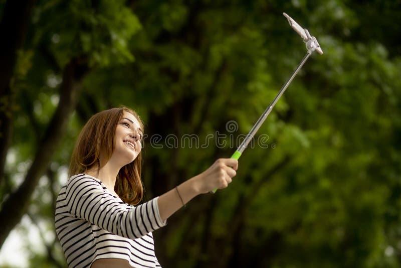 Счастливая девушка делая selfie для социальной сети в парке города лета на смартфоне на ручке selfie стоковая фотография