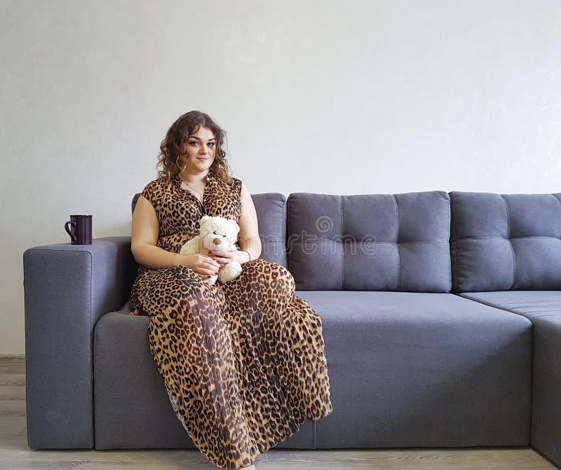 Счастливая девушка держать эмоций нежности игрушки плюшевого медвежонка софы ослабляет стоковые фото
