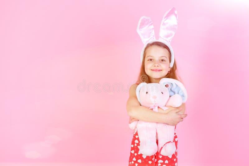 Счастливая девушка держа игрушку кролика на розовой предпосылке стоковое фото
