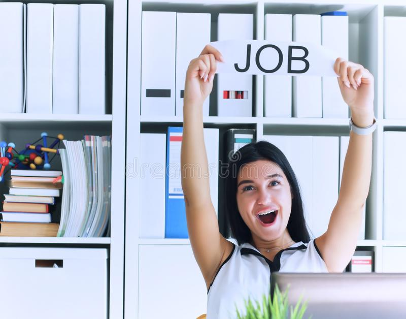 Счастливая девушка держа плакат с работой надписи Был интервьюирован и получил заявитель работу в офисе стоковое фото rf