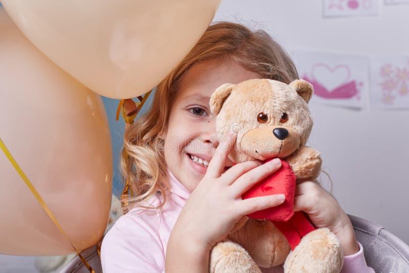 Счастливая девушка забавляясь с медведем стоковая фотография rf