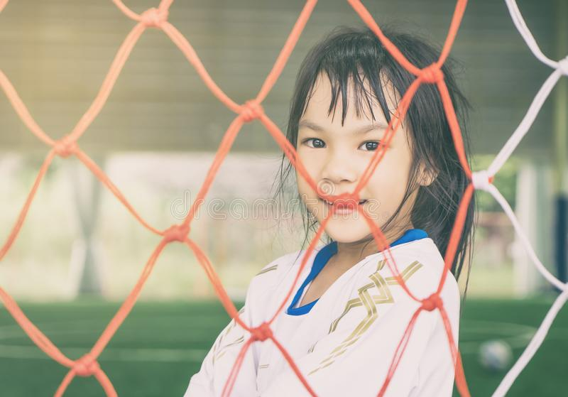 Счастливая девушка за сетью цели футбола футбола для концепции спорта стоковое изображение
