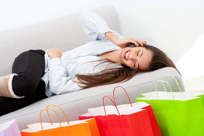 Счастливая девушка кладя на кресло с мобильным телефоном стоковое изображение rf
