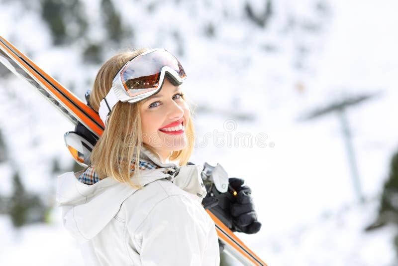 Счастливая девушка лыжника готовая для того чтобы кататься на лыжах в наклоне стоковое изображение