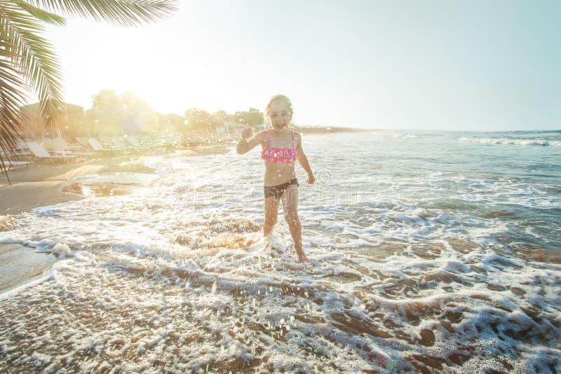 Счастливая девушка маленького ребенка играя на пляже моря и имея потеху стоковые изображения