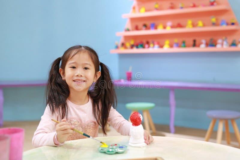 Счастливая девушка маленького ребенка имея потеху, который нужно покрасить на кукле штукатурки крытый стоковое изображение