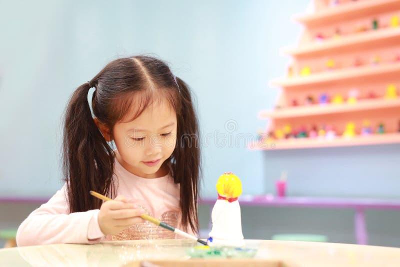 Счастливая девушка маленького ребенка имея потеху, который нужно покрасить на кукле штукатурки крытый стоковая фотография