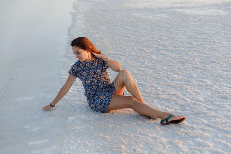 Счастливая девушка наслаждаясь заходом солнца, касается воде озера соли сидя на кристаллах стоковая фотография rf
