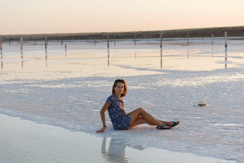 Счастливая девушка наслаждаясь заходом солнца, касается воде озера соли сидя на кристаллах стоковое изображение rf