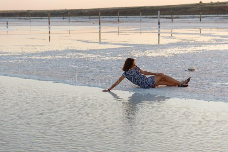 Счастливая девушка наслаждаясь заходом солнца, касается воде озера соли сидя на кристаллах стоковое фото rf