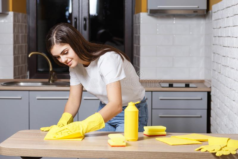 Счастливая девушка очищая кухню стоковая фотография rf