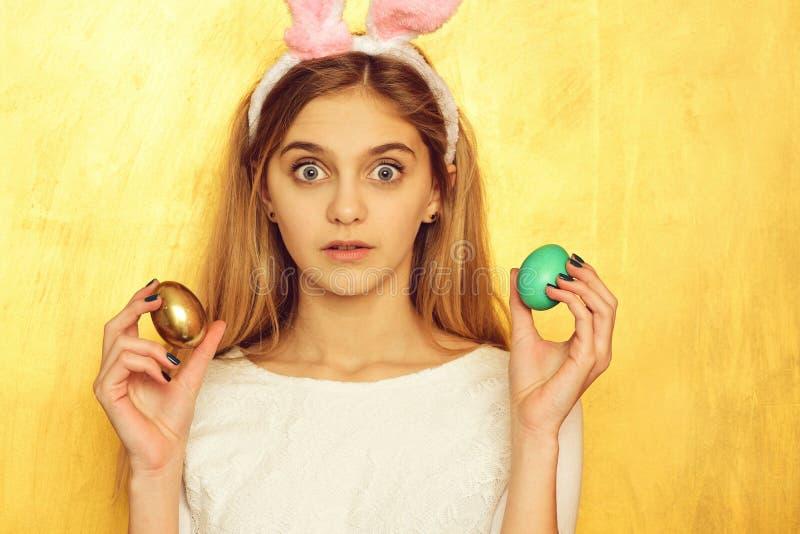 Счастливая девушка пасхи в ушах зайчика с золотым яйцом стоковые изображения rf