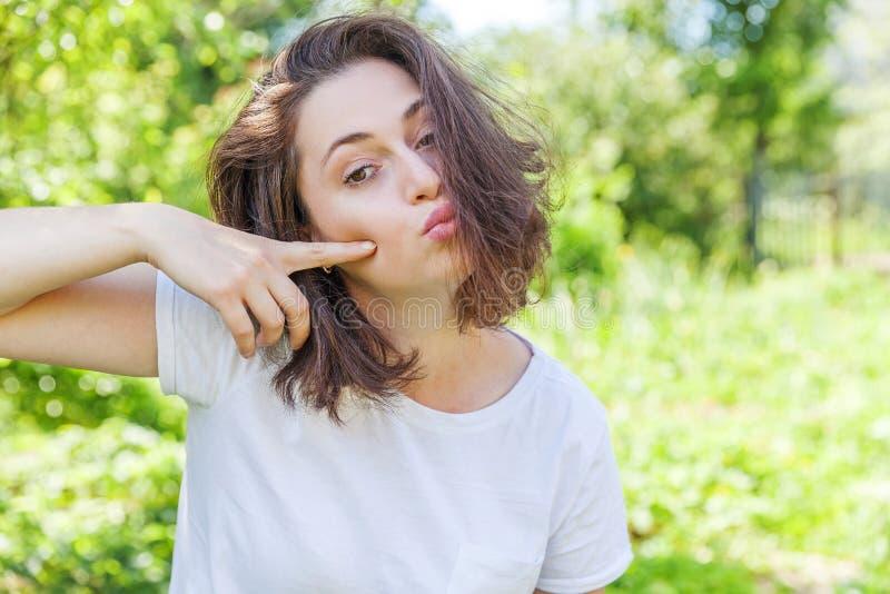 Счастливая девушка представляя с выражением стороны поцелуя Женщина брюнета портрета красоты молодая счастливая положительная на  стоковые изображения
