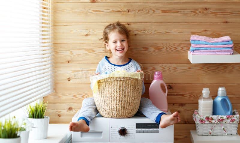 Счастливая девушка ребенка домохозяйки в прачечной с стиральной машиной стоковые фото