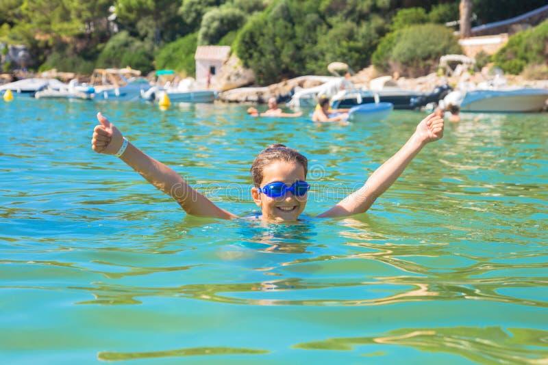Счастливая девушка ребенка плавает в море и показывает большие пальцы руки вверх по символу стоковая фотография