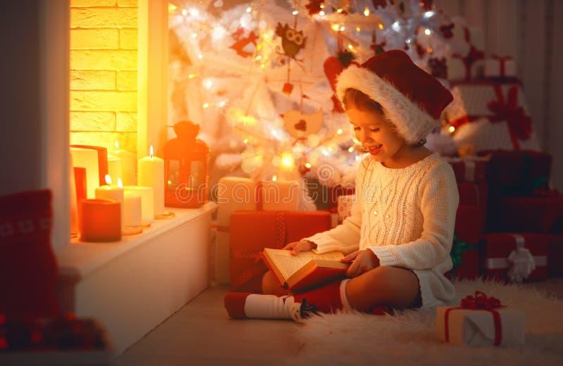 Счастливая девушка ребенка прочитала книгу на рождестве около камина дома стоковая фотография rf