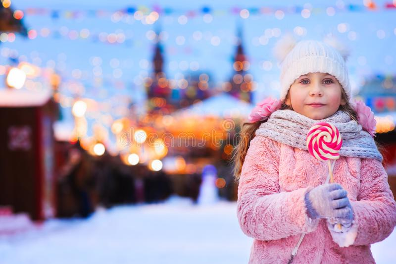 счастливая девушка ребенк с конфетой рождества Портрет зимнего отдыха в выравниваясь городе Москвы стоковая фотография