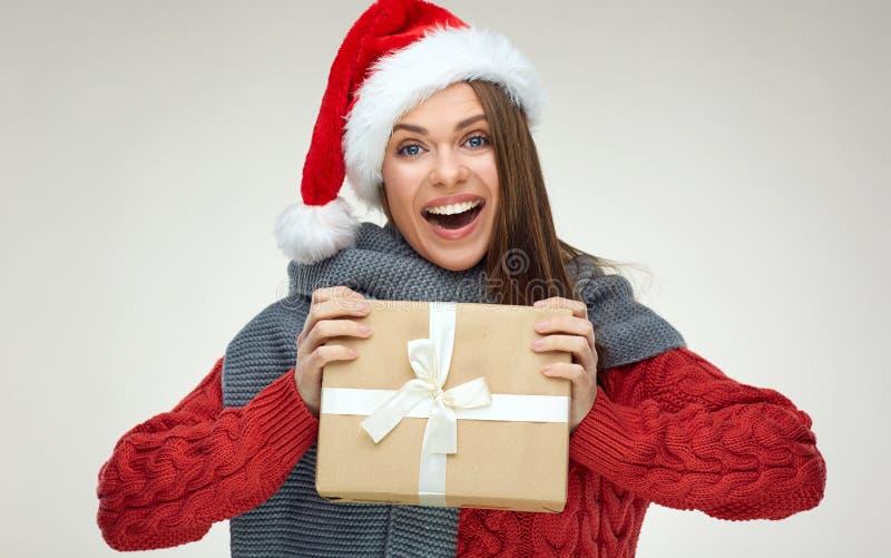 Счастливая девушка Санты держа подарок рождества, нося красную шляпу стоковое фото rf