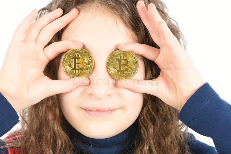 Счастливая девушка с длинным вьющиеся волосы держит bitcoin cryptocurrency 2 глаза вместо серебряное в руках на белой предпосылке стоковое фото rf