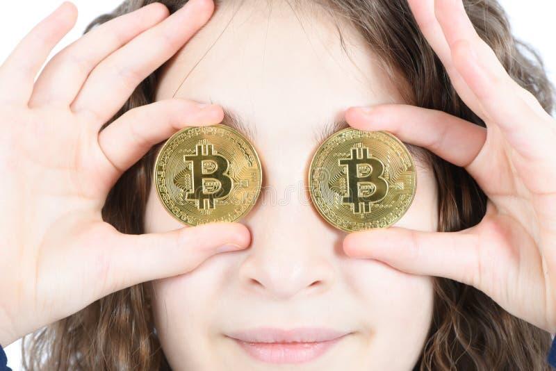 Счастливая девушка с длинным вьющиеся волосы держит bitcoin cryptocurrency 2 глаза вместо серебряное в руках на белой предпосылке стоковое изображение