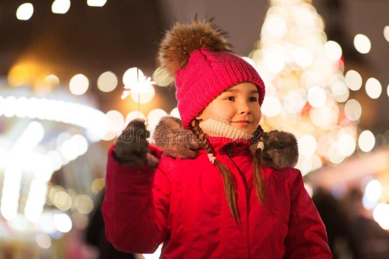 Счастливая девушка с игрушкой на рынке Рождества стоковое фото