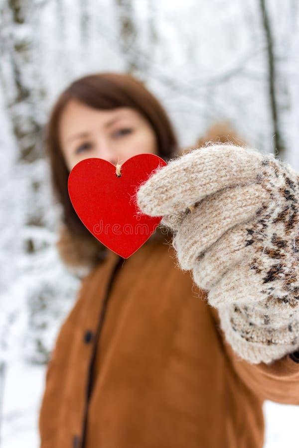 Счастливая девушка с красным деревянным сердцем держа в руках в предпосылке леса зимы несосредоточенной Праздники дня Святого Вал стоковые изображения