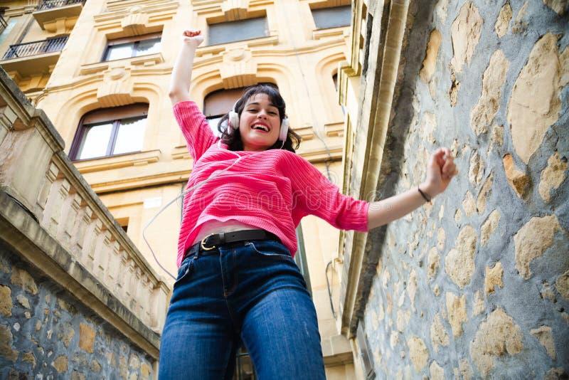 Счастливая девушка с наушниками танцуя в улице стоковое фото