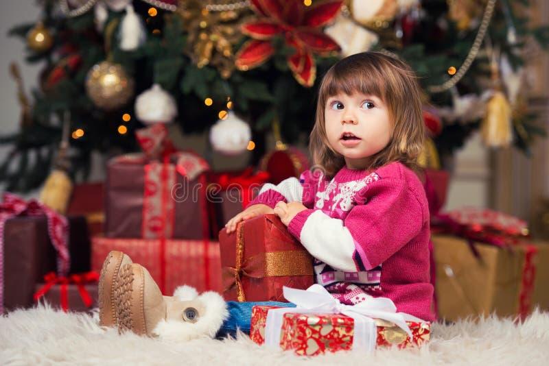 Счастливая девушка с подарком в руках на предпосылке дерева Нового Года стоковая фотография