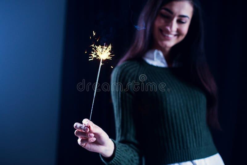 Счастливая девушка усмехаясь и держа сверкная фейерверк в ее руке стоковые фотографии rf
