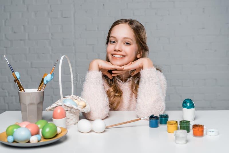 Счастливая девушка усмехаясь на камере пока сидящ на таблице с красками, корзиной и пасхальными яйцами стоковые фотографии rf
