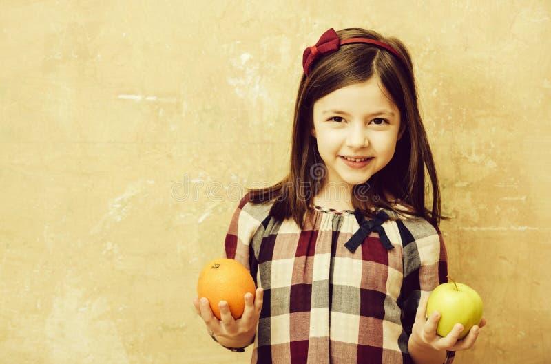 Счастливая девушка усмехаясь с апельсином и яблоком в руках стоковое изображение rf