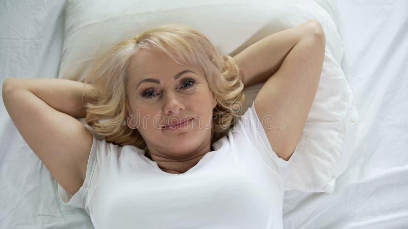 Счастливая достигшая возраста женщина лежа в кровати в утре, смотря в камере, здоровье и энергии стоковые фотографии rf