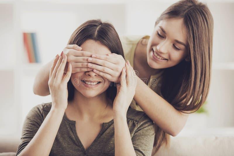 Счастливая дочь закрывает ее глаза матери с руками стоковое фото rf