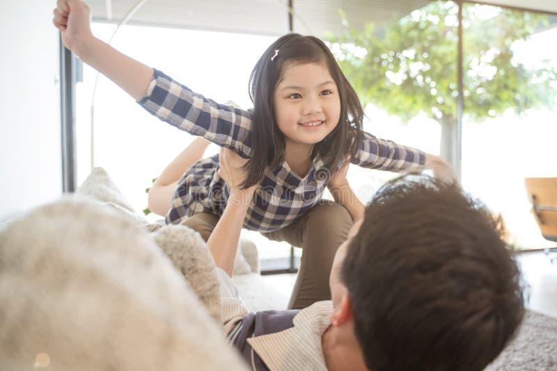 Счастливая дочь маленькой девочки играя с отцом пока задняя часть папы езды и папа лежа на кровати дома стоковое фото rf