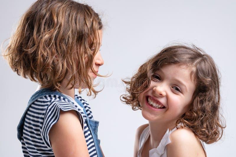 Счастливая дружелюбная привлекательная маленькая девочка с сестрой стоковые фото