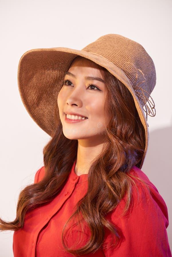 Счастливая думая молодая женщина смотря вверх в соломенной шляпе на белой предпосылке с пустым космосом экземпляра стоковое фото
