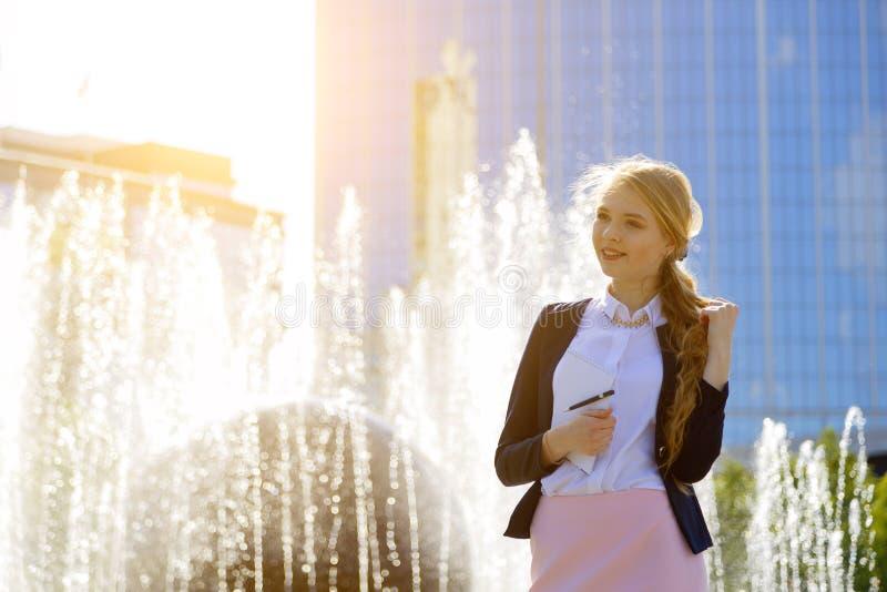 Счастливая европейская студентка с поднятым запястьем празднуя хорошие новости, проходящ outdoors экзамена или теста стоковая фотография rf