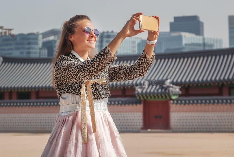 Счастливая европейская туристская женщина в национальном корейском костюме идет через дворцы с телефоном стоковое изображение rf