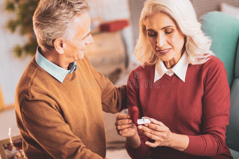 Счастливая жена смотря кольцо представленное супругом стоковое изображение rf